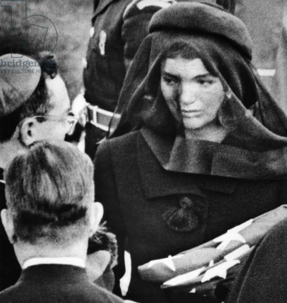 Jacqueline Kennedy at President John Kennedy's funeral. She receives the comfort of a priest after accepting the folded American flag that covered her late husband's coffin. Nov. 25, 1963