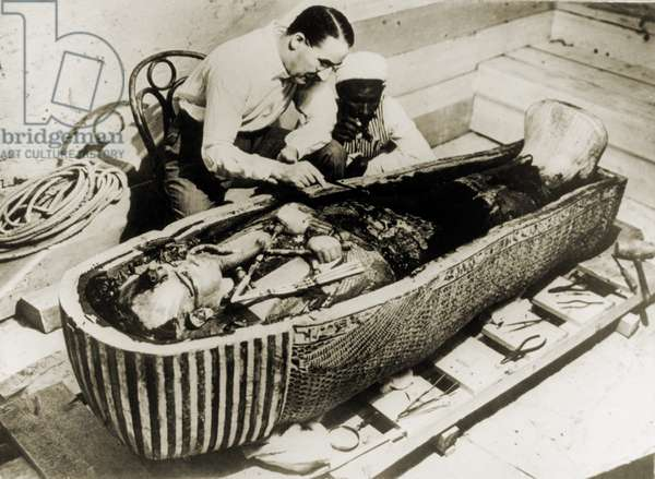 Howard Carter (1873-1939), seated beside coffin of King Tutankhamen, removing the consecration oils which covered the third or innermost coffin. 1926