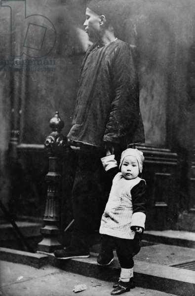 Chinese New Year, Chinese child with an adult on step outside of building, Chinatown, New York City, photograph, 1909