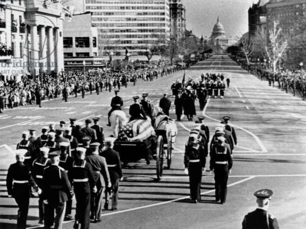 President Kennedy's flag-draped coffin moves slowly past mourning crowds. The funeral procession was on Pennsylvania Avenue traveling to the Capitol, where the assassinated President would lie in state for one day before his funeral. Nov. 24, 1963