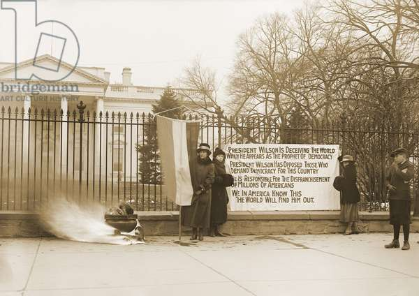 National Women's Party demonstration with a bonfire in front of the White House in 1918. The banner questions Wilson's commitment to democracy for his failure to support women's suffrage