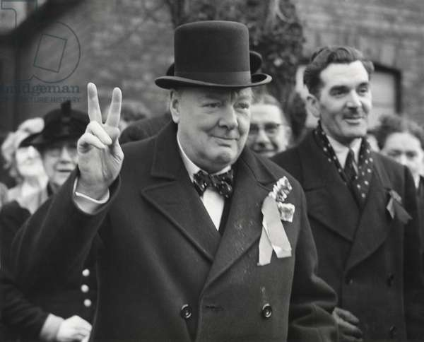 Conservative Party Leader Winston Churchill gives his familiar victory sign. He was making a last-minute campaign tour before the General Election. Woodford, Essex. Feb. 23, 1950.