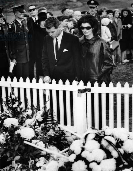 Jacqueline Kennedy and Attorney General Robert Kennedy visit the flower covered grave of President John Kennedy at Arlington National Cemetery. Nov. 27, 1963