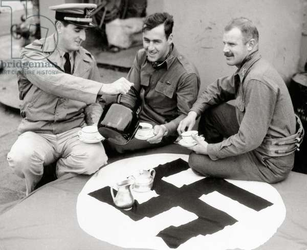 A U.S. Coast Guard is serving tea for two infantry officers, English Channel, 1944 (b/w photo)