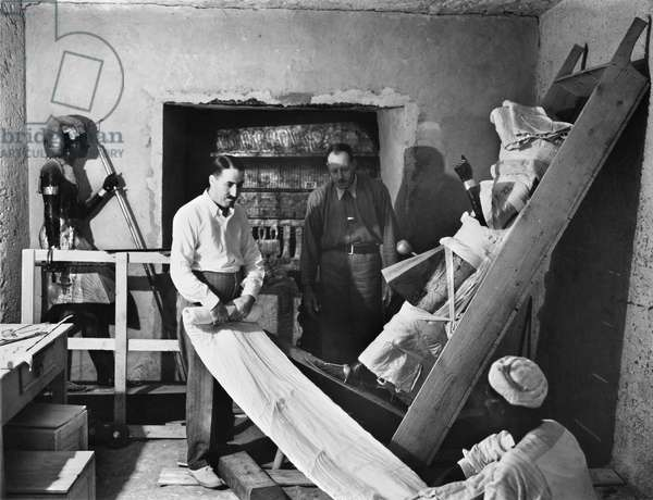 HOWARD CARTER (1873-1939) English archaeologist. Carter (in white shirt) and A.R. Callender in the antechamber of the tomb of Tutankhamen, wrapping up one of the two statues of the king for removal, 1923. Photographed by Harry Burton.