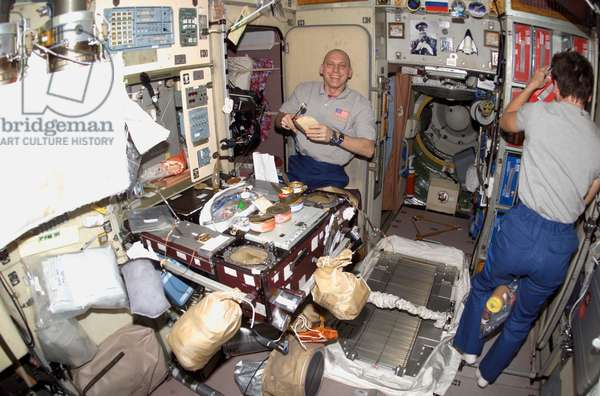 SPACE STATION, 2007 American astronaut Clay Anderson prepares a meal in the galley on board the Zvezda Service Module of the International Space Station. Photograph, 4 November 2007.