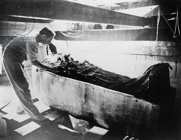 HOWARD CARTER (1873-1939) English archaeologist. Photographed with the sarcophagus of King Tutankhamen in the tomb in the Valley of the Kings, Egypt, c.1925.