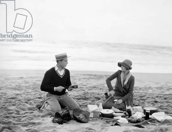SILENT FILM STILL: PICNIC. Beach picnic, late 1920s.
