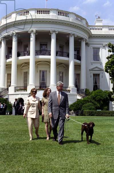 THE CLINTONS, 1998 President Bill Clinton, First Lady Hillary Rodham Clinton, Chelsea Clinton, and Buddy the Dog walking on the South Lawn of the White House in Washington, D.C. Photograph by Ralph Alswang, 1998.