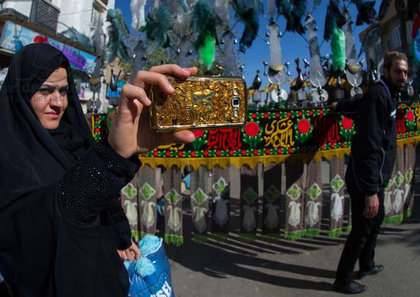 Iranian Woman Taking Pictures with a Mobile Phone Branded Louis Vuitton during Ashura, Kurdistan Province, Bijar, Iran (photo)