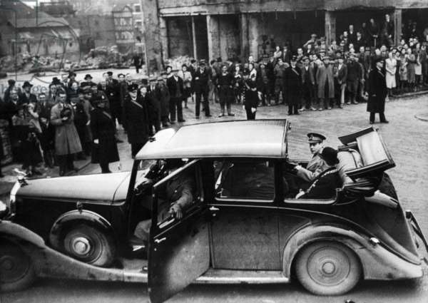 King George VI sits in the back of an open top car as he visits the bomb damaged city of Bristol following an air raid, December 1940 (b/w photo)