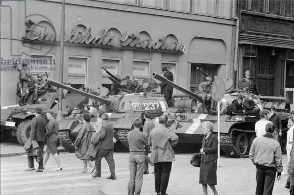 A Russian tank patrols in Wenceslas Square as locals walk by, at the end of the Prague Spring, August 1968 (b/w photo)