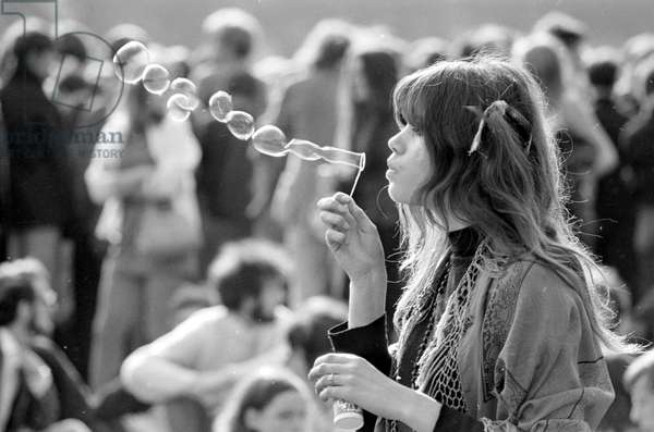 A hippy girl blowing bubbles at a pop concert, 1969 (b/w photo)