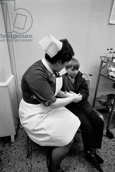 A young boy witha an injured hand gets treatment from a nurse Eliat the hospital, November 1969 (b/w photo)