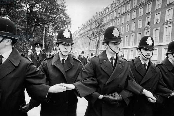 Young policemen lock arms as they prepare to take the strain for large crowds in Grosvenor Square at a mass anti Vietnam War rally, 27th October 1968 (b/w photo)