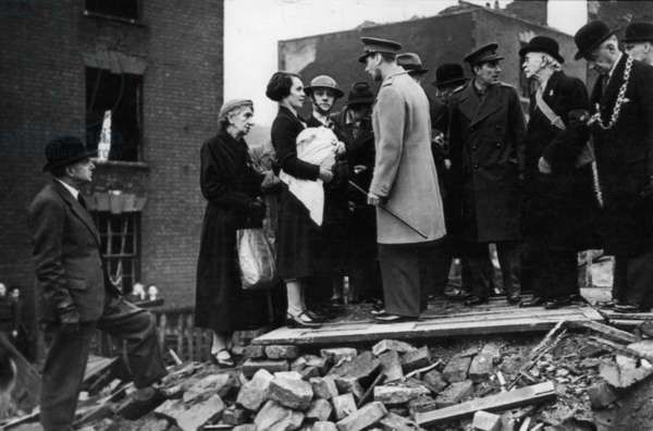 King George VI meets residents of a bombed street during his visit to the city of Bristol following an air raid, December 1940 (b/w photo)