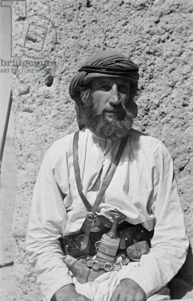 Half length portrait of Wilfred Thesiger in Arab dress outside of Al Muwaiji Fort in Al Ain, United Arab Emirates, April 6–9, 1949 (b/w photo)