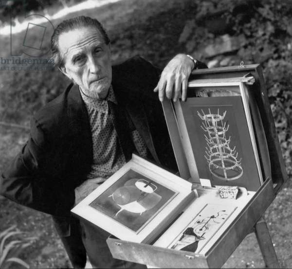 Marcel Duchamp with a box containing samples of his work, c.1957 (b/w photo)