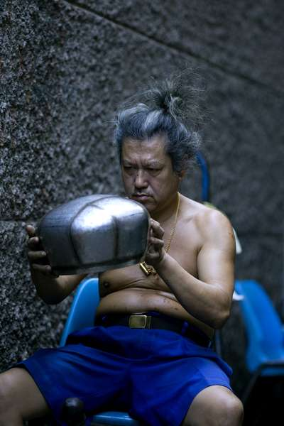 Man inspecting bowl for imperfections. Thailand, January 18, 2007.  (photo)