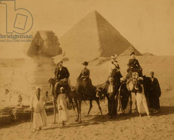 Three women and a man in western attire, seated on camels, several local men stand before the camels holding the reins, a pyramid and the sphinx in background 1880 (photo)