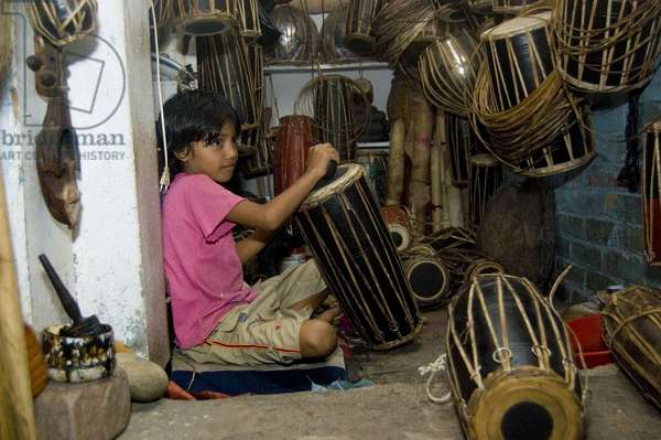 A young girl making a madal, a traditional nepali musical intrument. Kathmandu, Nepal. September 11, 2007.  (photo)