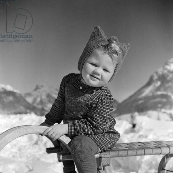 Little girl on her sleigh in winter time, Germany 1930s (b/w photo)