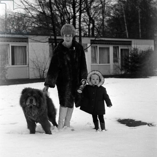 German actress Ingrid van Bergen playing with her daughter Carolin and their dog in the snow, Germany 1960s