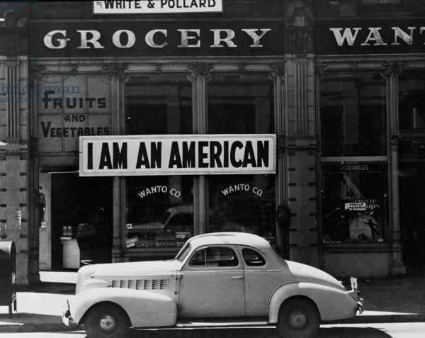 Japanese American shop owner in Oakland, California hopes to avoid internment after the bombing of Pearl Harbor, 1942 (b/w photo)