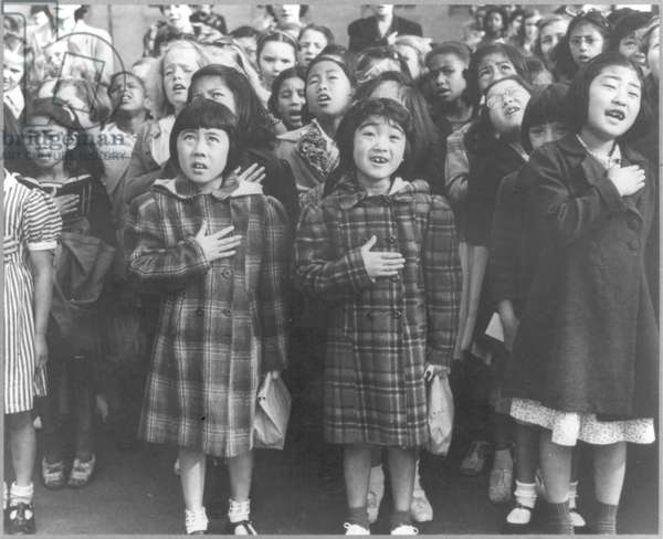 Children in a flag pledge ceremony including some of Japanese ancestry who will be housed in War Relocation Authority Centers, 1942 (b/w photo)
