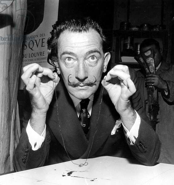 Painter Salvador Dali presenting artwork that will be destroyed by musket fire on November 16th 1956 (b/w photo)