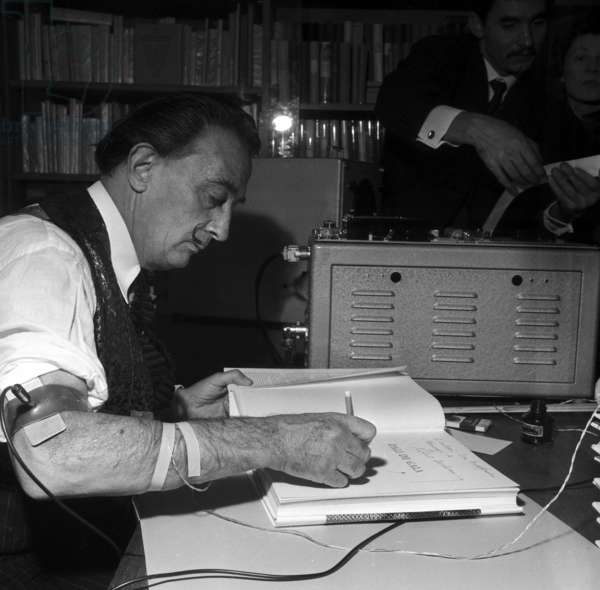Spanish painter Salvador Dali signing the book
