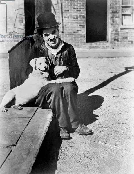 A dog 's life by and with Charlie Chaplin (the tramp) sitting in the street with the dog Mut (Scraps). Los Angeles (Chaplin Studios), 1918.